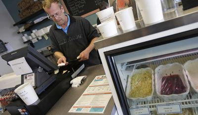 In this Tuesday, Jan. 28, 2014 photo, manager Randy Smith checks the register at Rascal's NY Deli in Cincinnati. Smith says overall business is down at the deli, because of the cold weather, but that their carryout and delivery business is up. (AP Photo)