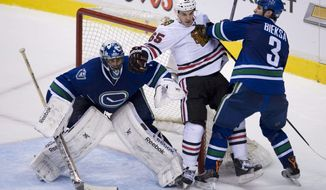 Vancouver Canucks defenceman Kevin Bieksa (3) tries to clear Chicago Blackhawks center Andrew Shaw (65) from in front of Vancouver Canucks goalie Roberto Luongo (1) during the third period of NHL action in Vancouver, British Columbia Wednesday, Jan. 29, 2014. (AP Photo/The Canadian Press, Jonathan Hayward)