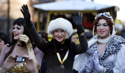 Actress Helen Mirren waves as she is accompanied by drag actors Tony Oblen, left, and Ethan Hardy, right, as she is paraded through Harvard Square as woman of the year by Harvard University's Hasty Pudding Theatricals in Cambridge, Mass., Thursday, Jan. 30, 2014. (AP Photo)