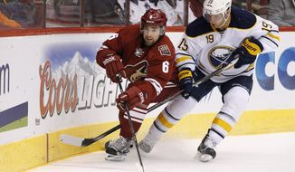 Phoenix Coyotes' David Schlemko (6) and Buffalo Sabres' Cody Hodgson (19) skate after the puck during the first period of an NHL hockey game on Thursday, Jan. 30, 2014, in Glendale, Ariz. (AP Photo)