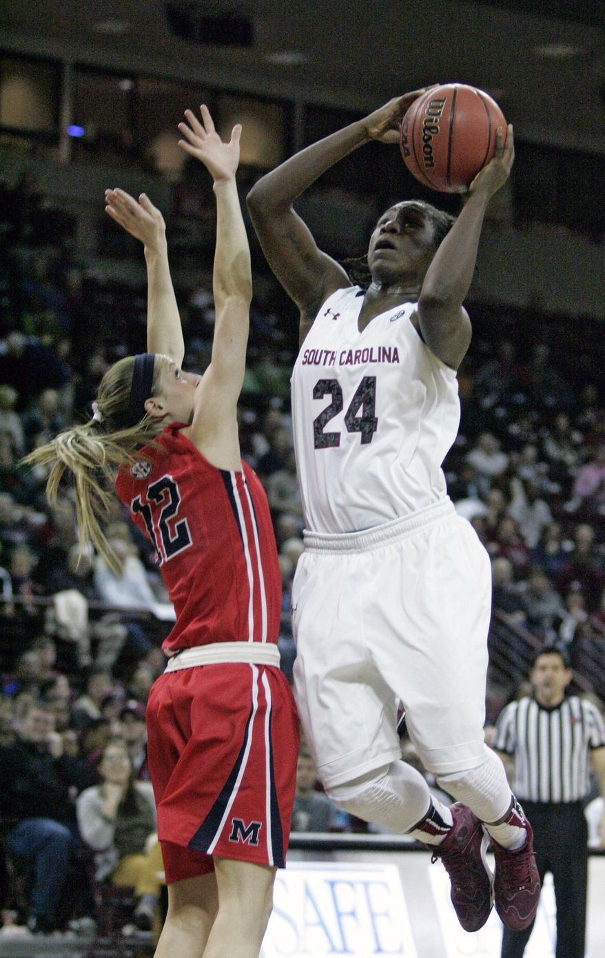 South Carolina's Aleighsa Welch (24) drives for the basket  as Ole Miss's Gracie Frizzell (12)  tries to block during the first half of an NCAA college basketball game Thursday, Jan. 30, 2014, in Columbia, S.C. (AP Photo/Mary Ann Chastain)
