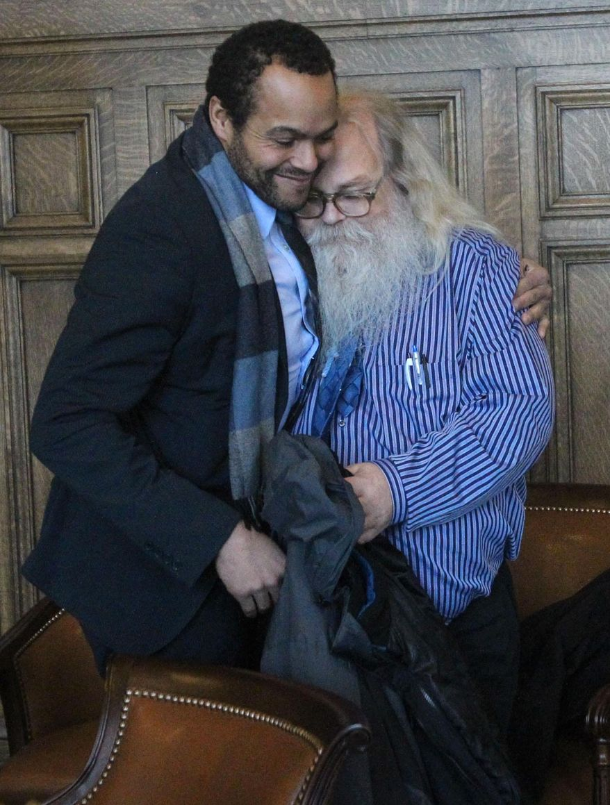 Attorney David Owens of the University of Chicago Exoneration Project, left, embraces Dewey Jones after a hearing before Summit County Common Pleas Court Judge Mary Margaret Rowlands on Thursday, Jan. 30, 2014 in Akron, Ohio. (AP Photo/Akron Beacon Journal, Michael Chritton)