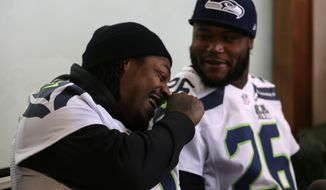 Seattle Seahawks running back Marshawn Lynch, left, laughs with teammate Michael Robinson as they participate in a media availability Thursday, Jan. 30, 2014, in Jersey City, N.J. The Seahawks and the Denver Broncos are scheduled to play in the Super Bowl XLVIII football game Sunday, Feb. 2, 2014. (AP Photo)