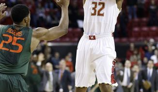 Maryland guard Dez Wells (32) shoots a go-ahead 3-pointer over Miami guard Garrius Adams in the final moments of an NCAA college basketball game in College Park, Md., Wednesday, Jan. 29, 2014. Wells contributed a team-high 21 points to Maryland's 74-71 win. (AP Photo/Patrick Semansky)
