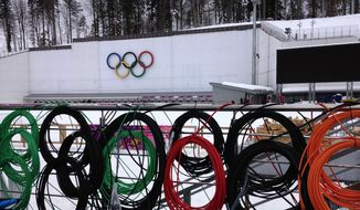 Cabling is coiled along a railing before being installed at the Laura Biathlon Center in preparation for the 2014 Winter Olympics in the Olympic Park, Monday, Jan. 27, 2014, in Krasnaya Polyana, Russia. (AP Photo/Tony Hicks)