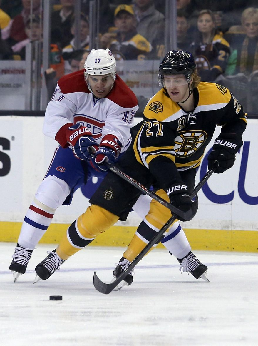 Boston Bruins defenseman Dougie Hamilton (27) controls the puck ahead of Montreal Canadiens left wing Rene Bourque (17) during the first period of an NHL hockey game on Thursday, Jan. 30, 2014, in Boston. (AP Photo/Mary Schwalm)
