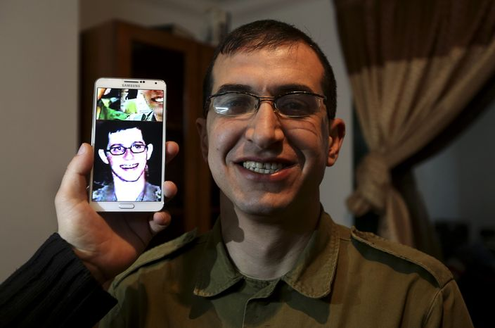 """In this Sunday, Jan. 26, 2014 photo, director Majed Jundiyeh holds a mobile phone to compare the image of Gilad Schalit to the likeness of actor Mahmoud Karira, who will play the character of Shalit in a movie being made in Gaza called, ''Losing  Shalit,"""" in Gaza City. """"Losing Schalit,"""" currently being filmed in the blockaded territory, is the first of a planned three-part series about the 2006 capture of Israeli soldier Gilad Schalit by gunmen allied with the Islamic militant Hamas movement. Parts two and three will depict Schalit's time in captivity and his 2011 swap for hundreds of Palestinian prisoners held by Israel. (AP Photo/Hatem Moussa)"""