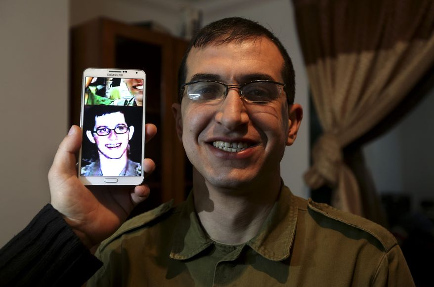 "In this Sunday, Jan. 26, 2014 photo, director Majed Jundiyeh holds a mobile phone to compare the image of Gilad Schalit to the likeness of actor Mahmoud Karira, who will play the character of Shalit in a movie being made in Gaza called, ''Losing  Shalit,"" in Gaza City. ""Losing Schalit,"" currently being filmed in the blockaded territory, is the first of a planned three-part series about the 2006 capture of Israeli soldier Gilad Schalit by gunmen allied with the Islamic militant Hamas movement. Parts two and three will depict Schalit's time in captivity and his 2011 swap for hundreds of Palestinian prisoners held by Israel. (AP Photo/Hatem Moussa)"