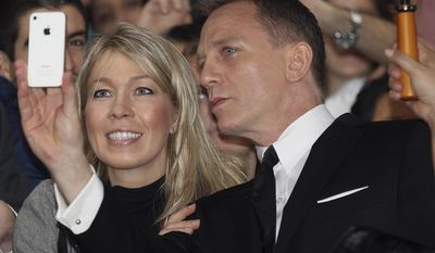 """FILE - This is a Nov. 16, 2012 file photo of actor Daniel Craig as he takes a photo with a fan in the crowd during the premier of the latest James Bond film, """"Skyfall""""  in Sydney, Australia.  A former tabloid reporter who admits illegally snooping on voicemails says he """"routinely"""" hacked the phone of actor Daniel Craig. Dan Evans has pleaded guilty to phone hacking while at the News of the World and the Sunday Mirror. He is a prosecution witness at the trial in London of former News of the World editors Andy Coulson and Rebekah Brooks, and five others. He told the jury on Thursday Jan. 30, 2014  """"I was routinely hacking Daniel Craig's phone from my Sunday Mirror days."""" He said he obtained a story about supermodel Kate Moss from Craig's voicemail messages. (AP Photo/Rob Griffith, File)"""