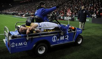Injured Atletico de Madrid's Filipe Luis of Brazil, leaves the pitch during their Spanish Copa del Rey round-8 second leg soccer match between Athletic Bilbao and Atletico de Madrid, at San Mames stadium, in Bilbao, northern Spain, Wednesday, Jan. 29, 2014.   (AP Photo/Alvaro Barrientos)