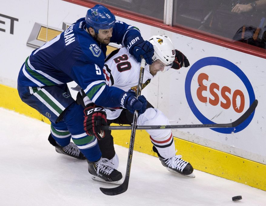 Vancouver Canucks right wing Zack Kassian (9) fights for control of the puck with Chicago Blackhawks left wing Brandon Saad (20) during the third period of NHL action in Vancouver, British Columbia Wednesday, Jan. 29, 2014. (AP Photo/The Canadian Press, Jonathan Hayward)