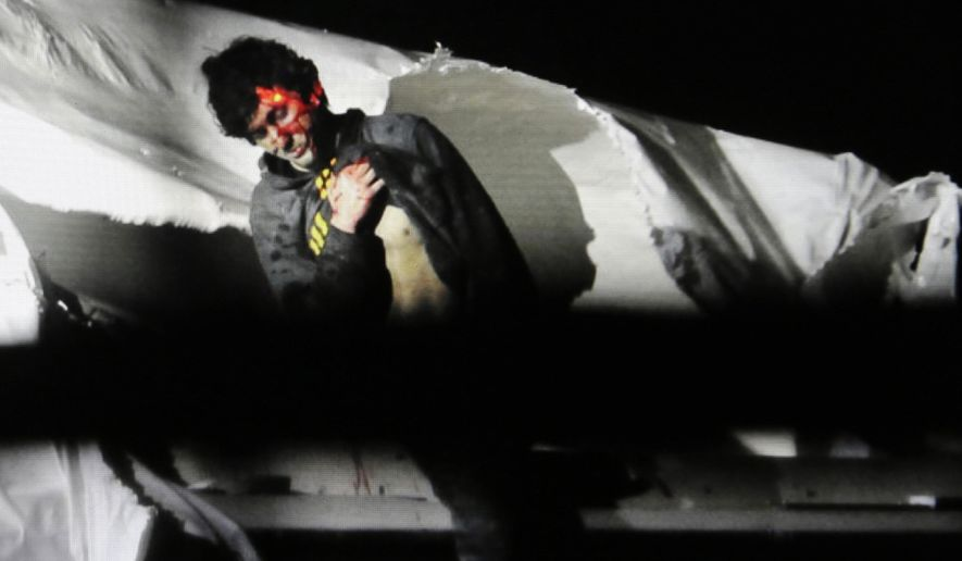 In this Friday, April 19, 2013, Massachusetts State Police file photo, 19-year-old Boston Marathon bombing suspect Dzhokhar Tsarnaev, bloody and disheveled with the red dot of a sniper's rifle laser sight on his head, emerges from a boat at the time of his capture by law enforcement authorities in Watertown, Mass. On Thursday, Jan. 30, 2014, U.S. Attorney General Eric Holder authorized the government to seek the death penalty in the case against Tsarnaev. (AP Photo/Massachusetts State Police, Sean Murphy, File)