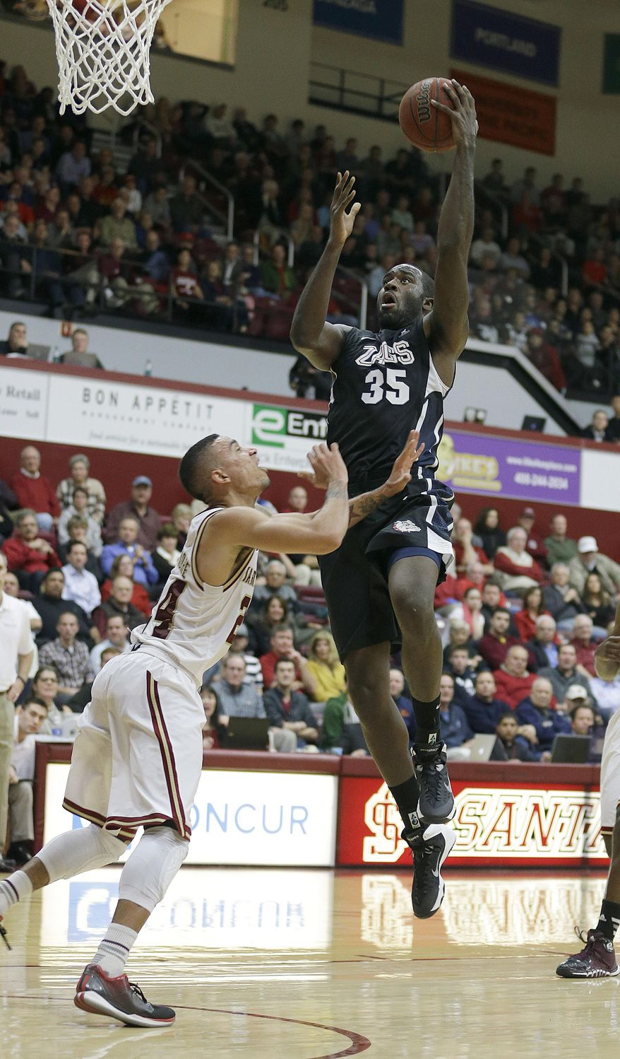 Gonzaga forward Sam Dower (35) drives the ball against Santa Clara guard Evan Roquemore in the first half of an NCAA college basketball game Wednesday, Jan. 29, 2014, in Santa Clara, Calif. (AP Photo/Tony Avelar)