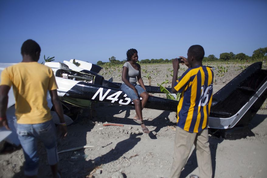 A woman poses for a photo while sitting on a Cessna Super Skymaster that made an emergency landing the night before in a field just outside Cabaret, a coastal town northwest of Port-au-Prince, Haiti, Thursday Jan. 30, 2014. Haitian police said on Thursday that the small plane piloted by a U.S. citizen suffered mechanical problems and made an emergency landing in the banana field. Police inspector Joachin Antoine said that pilot Practor Antoine was treated for unspecified injuries at a hospital in the capital. A passenger named John Michael was not injured. (AP Photo/Dieu Nalio Chery)