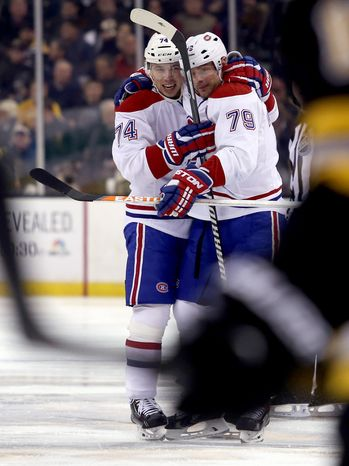 Montreal Canadiens defenseman Alexei Emelin (74) is congratulated by teammate Andrei Markov (79) after scoring a goal during the first period of an NHL hockey game against the Boston Bruins, Thursday, Jan. 30, 2014, in Boston. Markov assisted on the play. (AP Photo/Mary Schwalm)