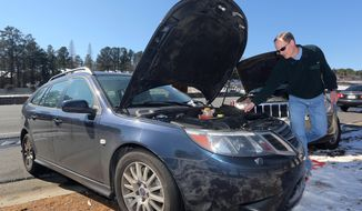 Kevin Krehmeyer helps a motorist get her car started on the side of Interstate 75, Thursday, Jan. 30, 2014, in Atlanta. The car was one of many vehicles abandoned during Tuesday's winter storm. (AP Photo/John Bazemore)