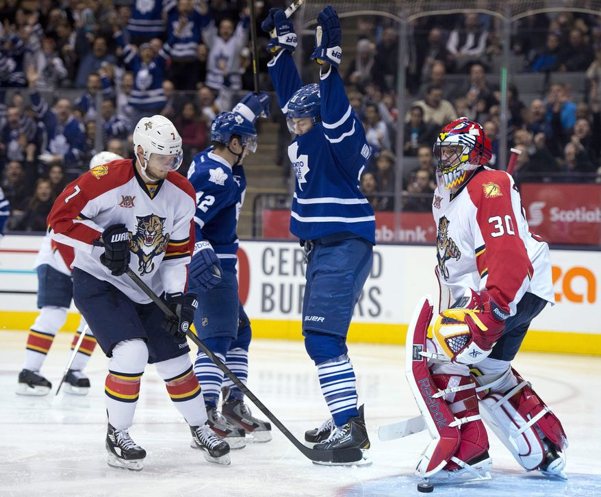 Toronto Maple Leafs left winger James van Riemsdyk (21) raises his arms to celebrate his goal with teammate Tyler Bozak (42) as Florida Panthers goaltender Scott Clemmensen and defenseman Dmitry Kulikov (7) react during the second period of an NHL hockey game in Toronto on Thursday, Jan. 30, 2014. (AP Photo/The Canadian Press, Frank Gunn)