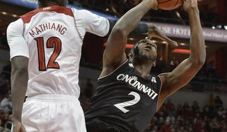 Cincinnati's Titus Rubles, right, puts up a shot past the defense of Louisville's Mangok Mathiang during the first half of an NCAA college basketball game Thursday, Jan. 30, 2014, in Louisville, Ky. (AP Photo/Timothy D. Easley)