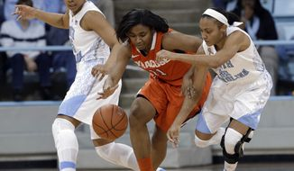Syracuse's Cornelia Fondren (11) chases the ball with North Carolina's Latifah Coleman (2) and Allisha Gray, left, during the first half of an NCAA college basketball game in Chapel Hill, N.C., Thursday, Jan. 30, 2014. (AP Photo)