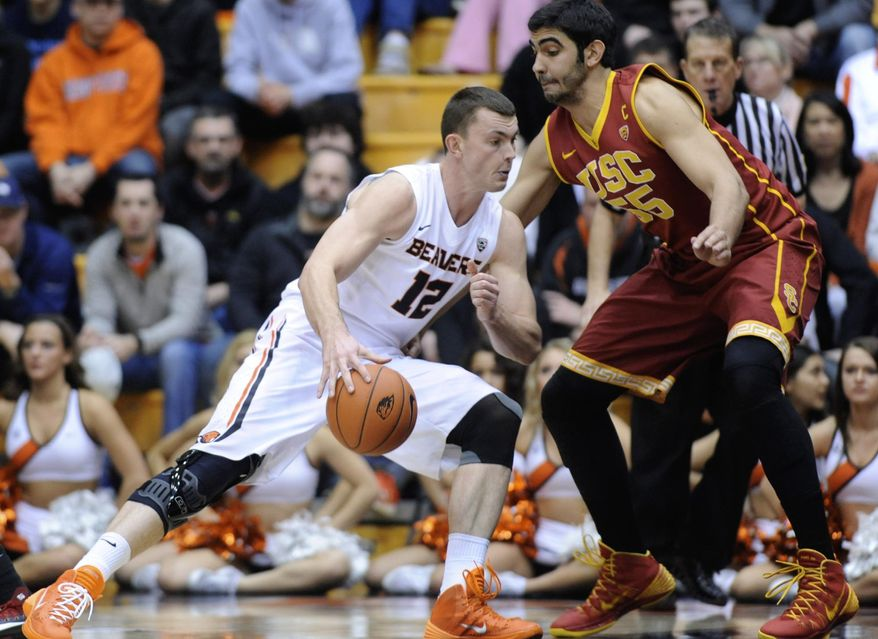 Southern California's Omar Oraby (55) defends against Oregon State's  Angus Brandt (12) during the first half of an NCAA college basketball game in Corvallis, Ore., Thursday Jan. 30, 2014.  (AP Photo/Greg Wahl-Stephens)