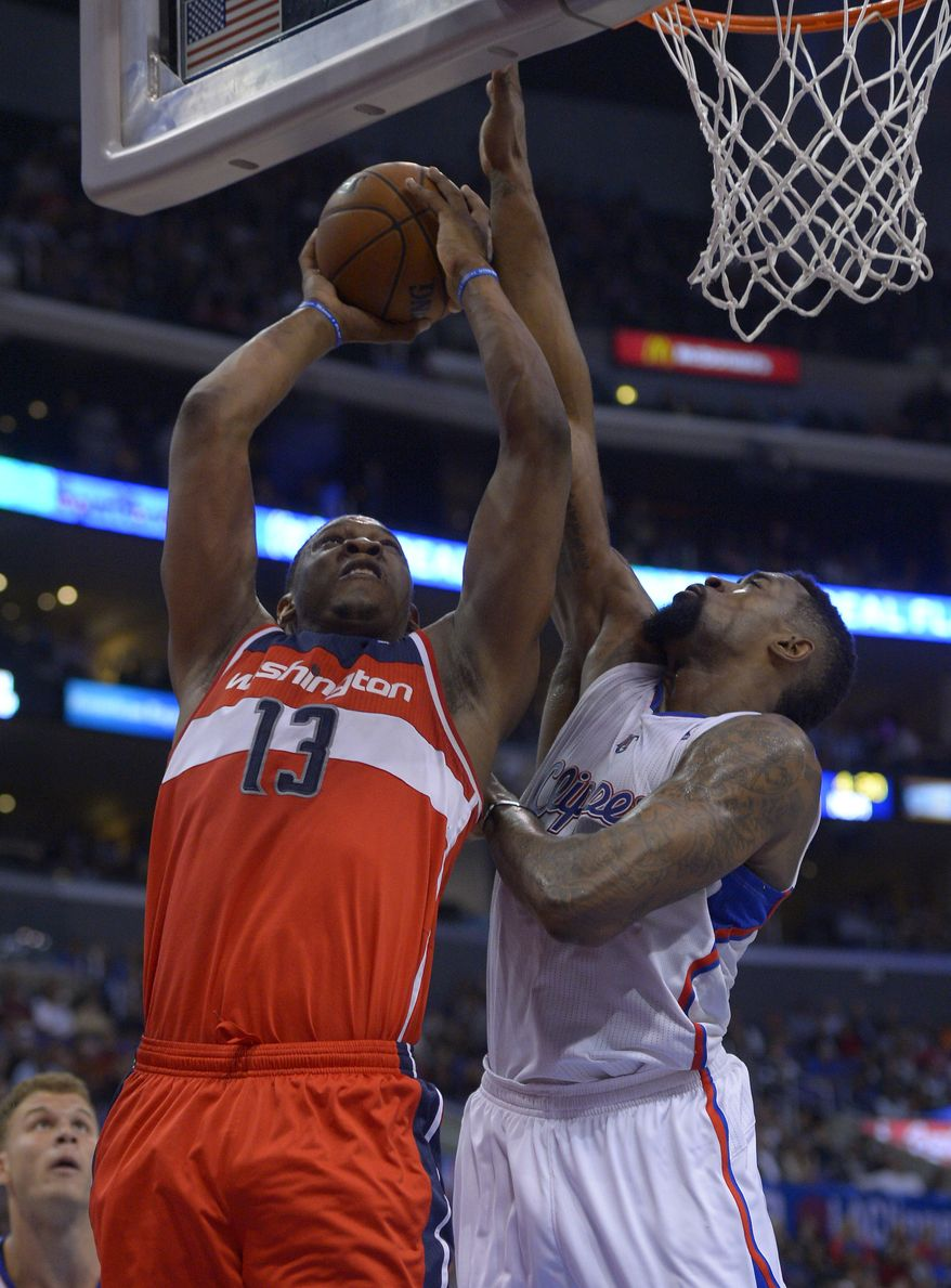 Washington Wizards center Kevin Seraphin, left, of France, puts up a shot as Los Angeles Clippers center DeAndre Jordan defends during the second half of an NBA basketball game, Wednesday, Jan. 29, 2014, in  Los Angeles. (AP Photo/Mark J. Terrill)