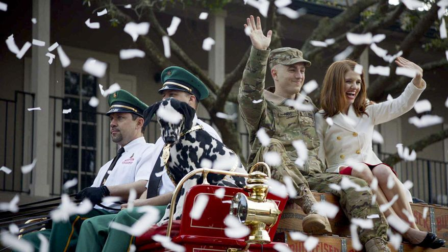 In this undated photo provided by Anheuser-Busch, Lt. Chuck Nadd and his girlfriend Shannon Cantwell wave as they ride on the wagon pulled by Clydesdales aboard the famously-red Budweiser beer wagon in a parade, led by a marching band in Winter Park, Fla. The brewer has fashioned an ad around the parade that will run during the Super Bowl.(AP Photo/Anheuser-Busch, Hand Out)