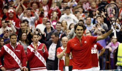 Switzerland's Roger Federer celebrates after winning his match over Ilija Bozoljac of Serbia during their Davis Cup World Group play-off first round tennis match between Serbia and Switzerland, in Novi Sad, Serbia, Friday, Jan. 31, 2014.  (AP Photo/Darko Vojinovic)