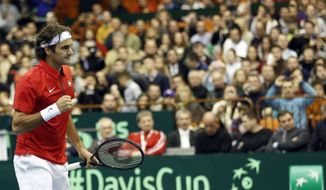 Switzerland's Roger Federer celebrates after winning his match over Ilija Bozoljac of Serbia during their Davis Cup World Group play-off first round tennis match between Serbia and Switzerland, in Novi Sad, Serbia, Friday, Jan. 31, 2014.  (AP Photo/Darko Vojinovic)