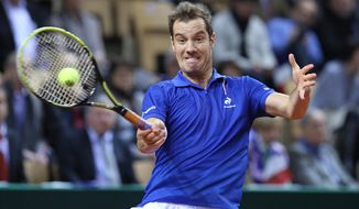 France's Richard Gasquet returns the ball to Australia's Nick Kyrgios during their single match, in the first round of the Davis Cup between France and Australia, in La Roche sur Yon, western France, Friday Jan. 31, 2014.(AP Photo/Remy de la Mauviniere)