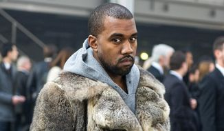 FILE - This Jan. 17, 2014 file photo shows singer Kanye West as he arrives for the Givenchy men's Fall-Winter 2014-2015 fashion collection in Paris.  West will not face criminal charges over an incident in which he apparently punched a man in a Beverly Hills chiropractor's office, prosecutors determined Friday, Jan. 31. The Los Angeles County District Attorney's Office rejected a battery case against the rapper because he had reached a civil settlement with the man and there were no significant injuries documented after the altercation. The altercation occurred after the 18-year-old man used a racial slur in an argument with West's fiancee, Kim Kardashian, on Jan. 13, according to a document prepared by a prosecutor.  (AP Photo/Zacharie Scheurer, File)