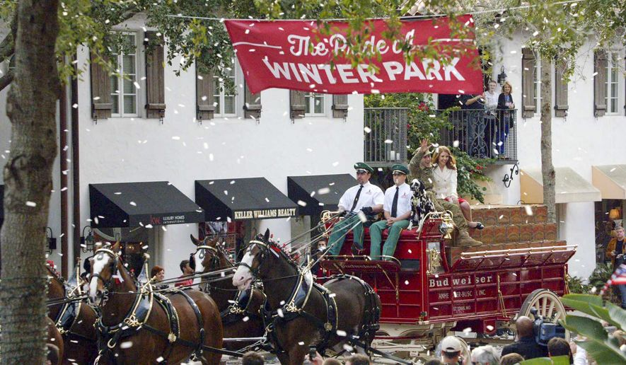 In this undated photo provided by Anheuser-Busch, Lt. Chuck Nadd and his girlfriend Shannon Cantwell wave as they ride aboard the famously-red Budweiser beer wagon pulled by Clydesdales in a parade, led by a marching band in Winter Park, Fla. The brewer has fashioned an ad around the parade that will run during the Super Bowl.(AP Photo/Anheuser-Busch, Hand Out)