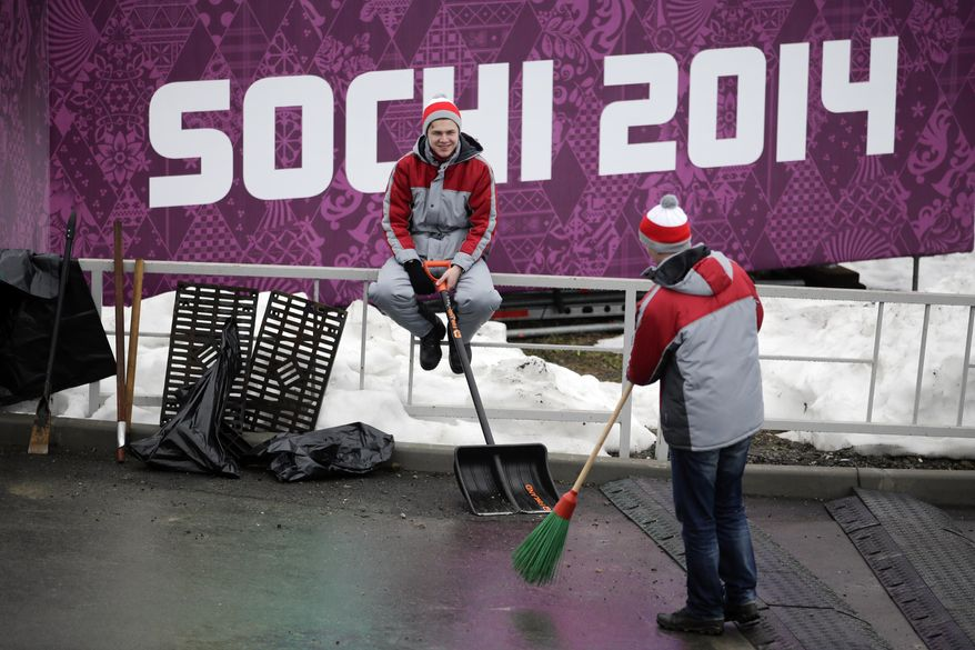 Two workers take a break at the Sanki Sliding Center, a venue for bobsleigh, skeleton and luge at the 2014 Winter Olympics, Friday, Jan. 31, 2014, in Krasnaya Polyana, Russia. (AP Photo/Jae C. Hong)