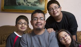 This photo taken Dec. 26, 2013, shows a portrait of Luis Rivera, 30, and his children, Angel, 11, left, Luis, 13, and Princess, 10, in their north Houston home. Rivera is a single father raising three children. (AP Photo/ Houston Chronicle, Johnny Hanson)