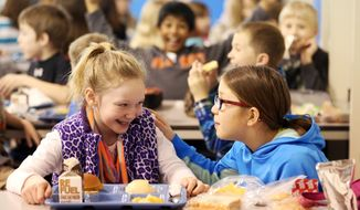 """** FILE ** In this Jan. 29, 2014 photo, third-graders Clare Vosberg-Padget, left, and Emily Morgan talk during lunch at Hoover Elementary School in Dubuque, Iowa. Vosberg-Padget, 8, has become the driving force behind the installation of a """"buddy bench"""" at her school, where children can signal to others that they'd like a playmate. (AP Photo/The Telegraph Herald, Jessica Reilly)"""