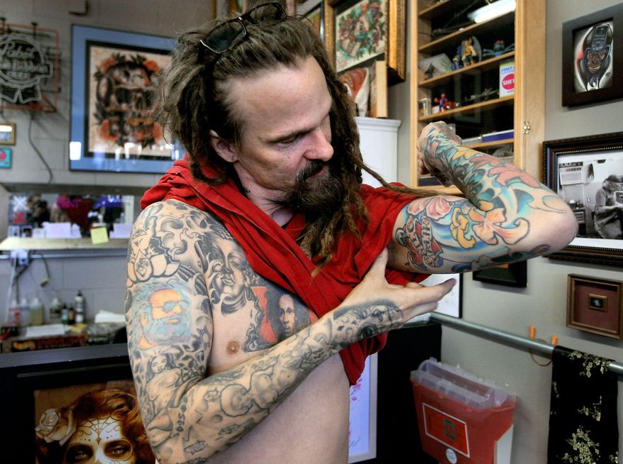 ** FILE ** In this Jan. 16, 2014 photo, Tattoo artist, Brandon Hudson, shows his tattoos at Roses and Ruins Tattoo Shop in North Charleston, S.C.  (AP Photo/The Post And Courier, Paul Zoeller)