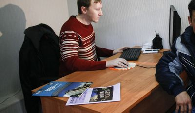 FILE - In this Jan. 30, 2013 file photo, Semyon Simonov helps a migrant worker at his office in Sochi, where he provides free legal aid to workers building Olympic venues. A lawyer for Simonov and Moscow-based prisoner rights activist Nikolai Levshits said Friday, Jan. 31, 2014, that the two men have filed a lawsuit against the Sochi Olympics organizers after they were barred from attending the games. Simonov has documented widespread abuse of migrant workers at Olympic construction sites. (AP Photo/Igor Yakunin, File)