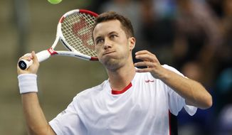 Germany's Philipp Kohlschreiber hits the ball in celebration after beating Spain's Roberto Bautista Agut during a Davis Cup World Group first round tennis match between Germany and Spain in Frankfurt, Germany, Friday, Jan. 31, 2014. (AP Photo/Michael Probst)