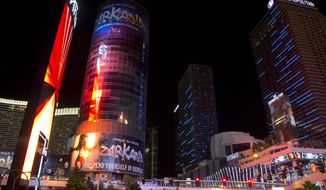 File- This June 2, 2013, file photo shows the Harmon Hotel tower, left, glowing in the light of an electronic marquee along the Strip, in Las Vegas. Clark County District Judge Elizabeth Gonzalez issued an order on Friday Jan. 31, 2014, requiring the casino owners to postpone demolishing the tower. (AP Photo/Julie Jacobson, File)