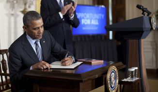 President Barack Obama signs a memorandum directing the federal government not to discriminate against those long-term unemployed workers in its own hiring practices in the East Room of the White House, as Vice President Joe Biden stands right, Friday, Jan. 31, 2014, in Washington. (AP Photo/Carolyn Kaster)