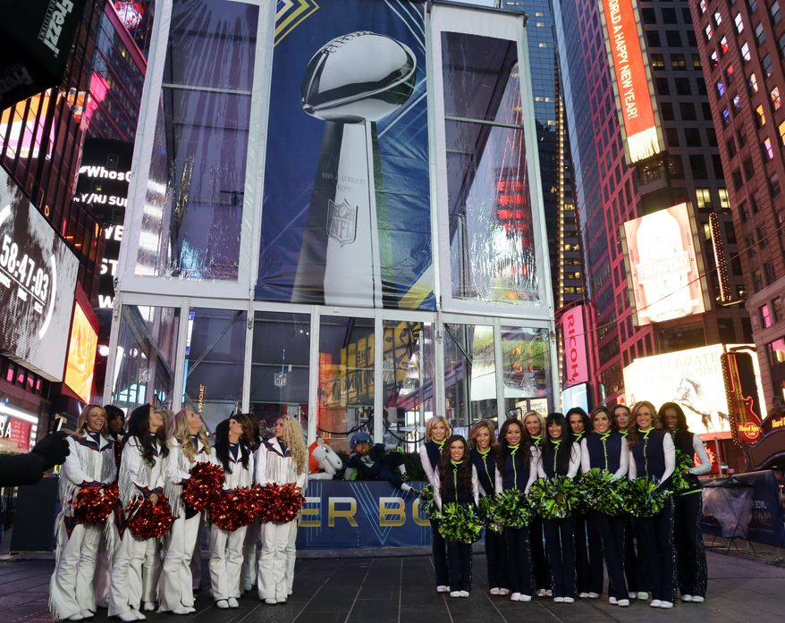 Denver Broncos cheerleaders and Seattle Seahawks Sea Gals cheerleaders stand in front of a photo of the Vince Lombardi Trophy, Friday, Jan. 31, 2014 during a live broadcast of Good Morning America at Times Square in New York. The Seattle Seahawks will play the Broncos Sunday in the NFL Super Bowl XLVIII football game in East Rutherford, N.J. (AP Photo/Ted S. Warren)