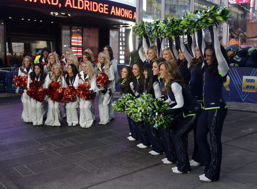 Denver Broncos cheerleaders and Seattle Seahawks Sea Gals cheerleaders cheer, Friday, Jan. 31, 2014 during a live broadcast of Good Morning America at Times Square in New York. The Seattle Seahawks will play the Broncos Sunday in the NFL Super Bowl XLVIII football game in East Rutherford, N.J. (AP Photo/Ted S. Warren)