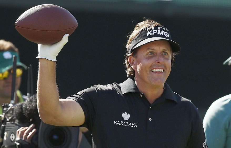 Phil Mickelson smiles as he gets ready to throw a football into the stands at the 16th hole during the third round of the Phoenix Open golf tournament Saturday, Feb. 1, 2014, in Scottsdale, Ariz. (AP Photo/Ross D. Franklin)