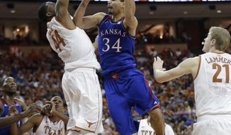 Kansas' Perry Ellis (34) shoots as Texas' Prince Ibeh (44) defends during the second half of an NCAA college basketball game, Saturday,  Feb. 1, 2014, in Austin, Texas. Texas won 81-69. (AP Photo/Eric Gay)