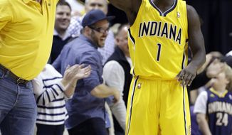 Indiana Pacers guard Lance Stephenson celebrates with a fan in the closing second of the second half of an NBA basketball game in Indianapolis, Saturday, Feb. 1, 2014. The Pacers defeated the Nets 97-96. (AP Photo/Michael Conroy)