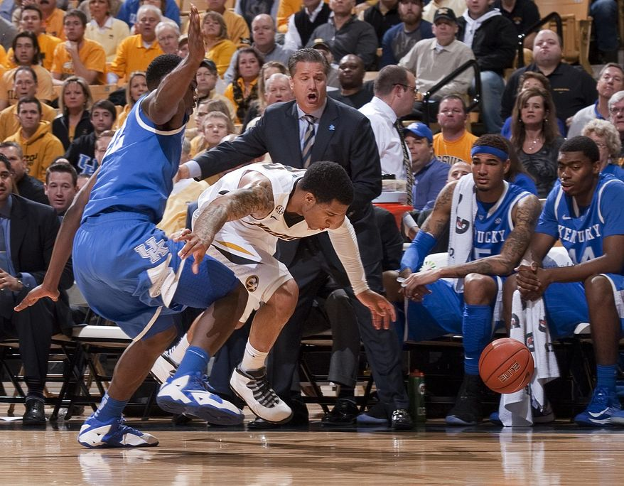 Missouri's Jabari Brown, right, looses the ball in front of the Kentucky bench as Kentucky's Alex Poythress, left, defends during the first half of an NCAA college basketball game Saturday, Feb. 1, 2014, in Columbia, Mo. (AP Photo/L.G. Patterson)