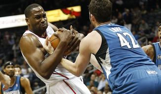 Atlanta Hawks forward Elton Brand and Minnesota Timberwolves Kevin Love, right, struggle for a rebound in the first half of an NBA basketball game, Saturday, Feb. 1, 2014, in Atlanta. (AP Photo/John Bazemore)
