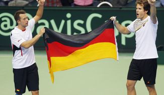 Germany's double Philipp Kohlschreiber, left, and Tommy Haas celebrate with the German flag after beating Spain's Fernando Verdasco and David Marrero during a Davis Cup World Group first round tennis match between Germany and Spain in Frankfurt, Germany, Saturday, Feb. 1, 2014. After winning the double, Germany has now a 3-0 lead and advances to the next round. (AP Photo/Michael Probst)