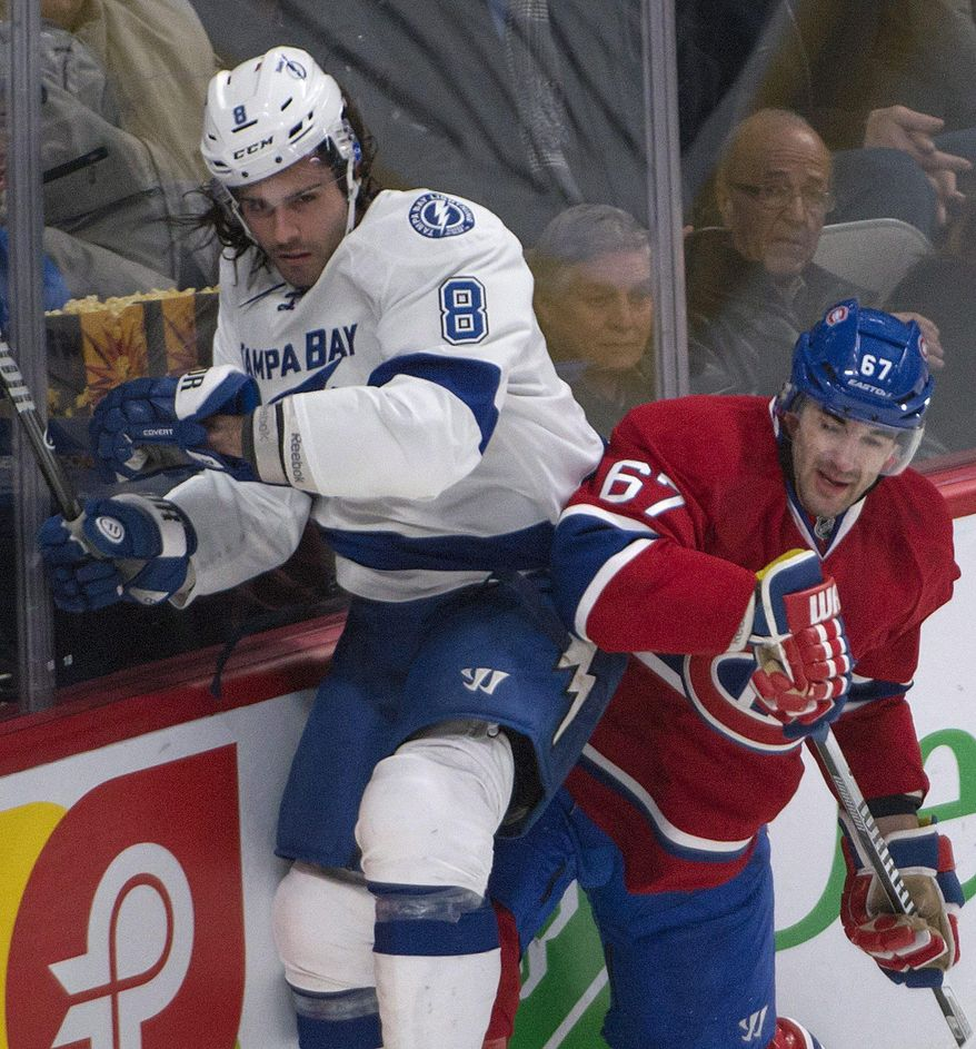 Montreal Canadiens' Max Pacioretty,right, checks Tampa Bay Lightning Mark Barberio during the first period of an NHL game in Montreal, Saturday, Feb. 1, 2014. (AP Photo/The Canadian Press, Peter McCabe)