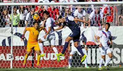 United States defender Omar Gonzalez (4) heads the ball as South Korea defender Kim Kee-Hee, center,  and goalkeeper Jung Sung-Ryong (1) defend during the first half of an international friendly soccer match in Carson, Calif., Saturday, Feb. 1, 2014. (AP Photo/Gus Ruelas)