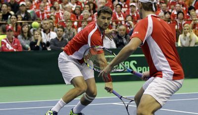 Switzerland's Michael Lammer, left, returns a ball as Marco Chiudinelli looks on during their Davis Cup World Group play-off first round doubles tennis match against Nenad Zimonjic and Filip Krajinovic of Serbia, in Novi Sad, Serbia, Saturday, Feb. 1, 2014. (AP Photo/Darko Vojinovic)
